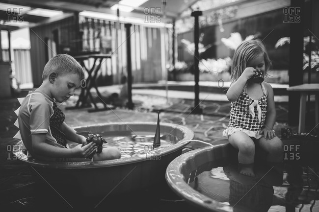 Two children playing in small wading pools