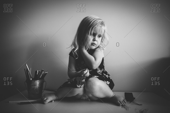 Little girl sitting on a desk with colored pencils
