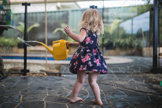 Little girl twirling around with a watering can
