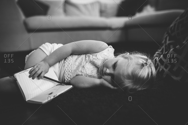 Little girl lying on a the floor with a notepad and pencil