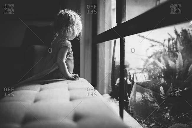 Side view of little girl looking out a window