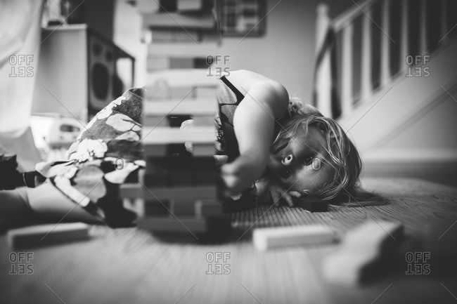Little girl lying on a the floor playing with a block game