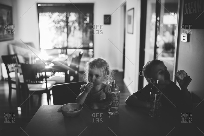 Children eating a snack at the kitchen counter