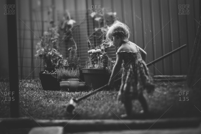 Little girl raking in her backyard