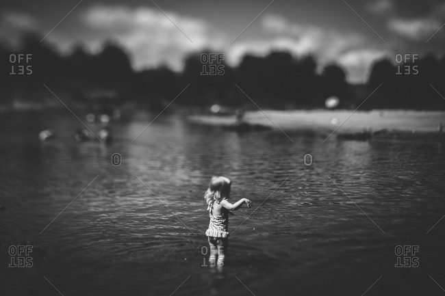Little girl searching for sticks in a lake