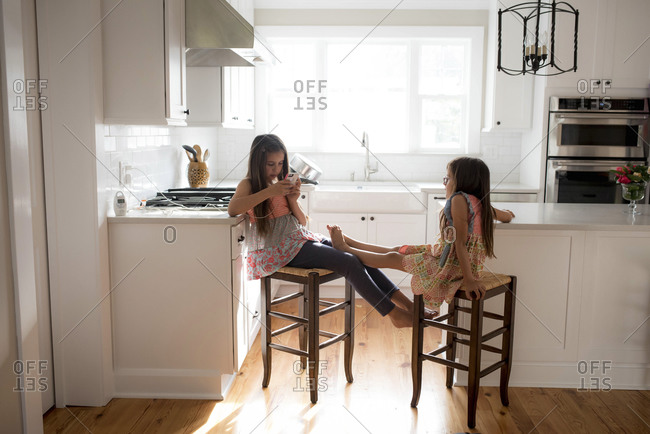 Marvelous Two Girls Sitting On Bar Stools In The Kitchen With Their Creativecarmelina Interior Chair Design Creativecarmelinacom