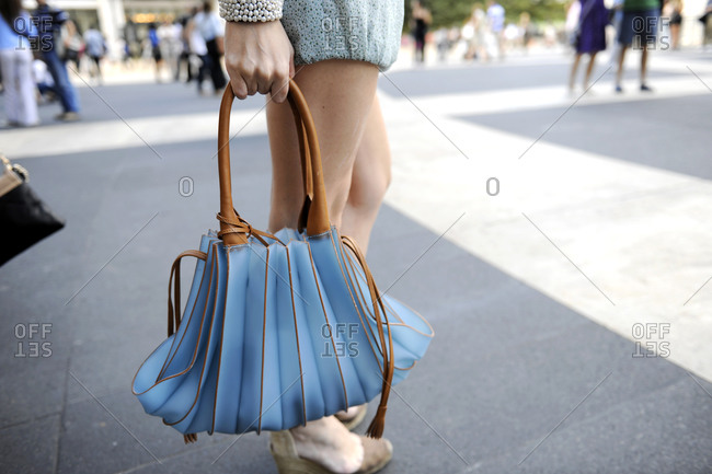 Woman carrying a blue purse with accordion folds