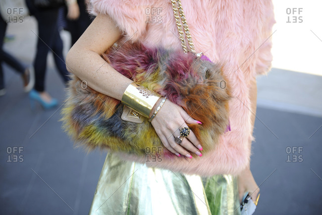 Woman in a fur shirt carrying a fur purse
