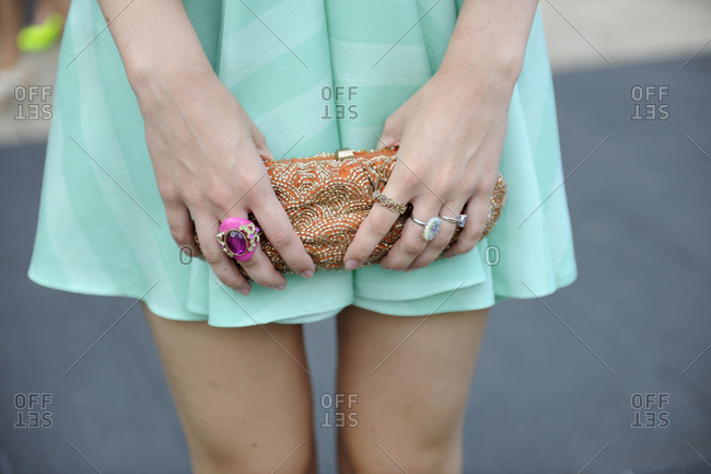 Woman in a teal striped skirt holding a beaded clutch