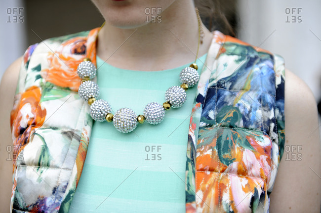 Woman wearing a floral vest and chunky beaded necklace