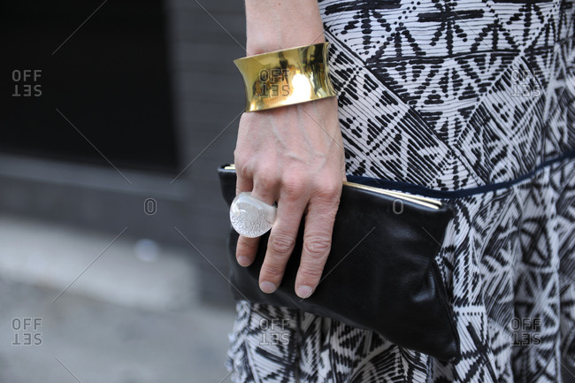 Woman in a black and white dress with a chunky ring and clutch