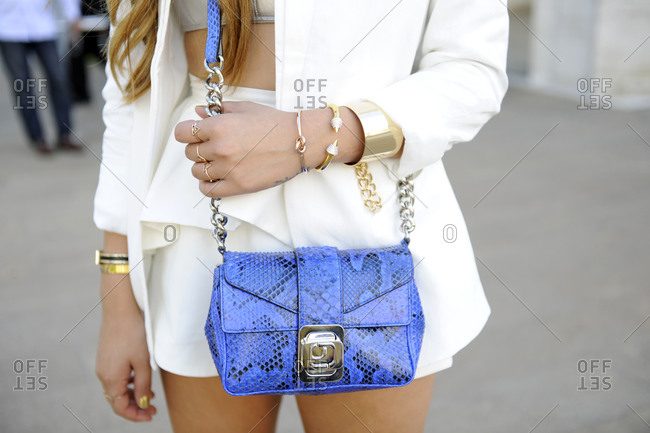 Woman in a white blazer and shorts with a blue snakeskin purse