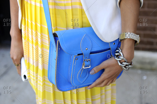 Woman in yellow pleated dress with a blue purse