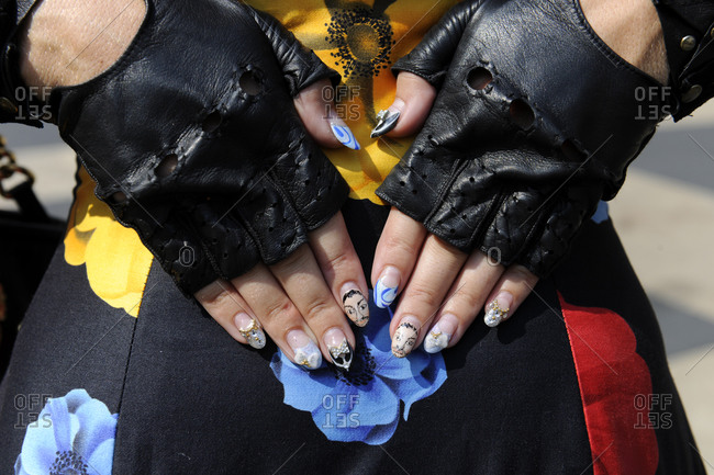Woman in a floral dress with leather fingerless gloves and designer fingernails