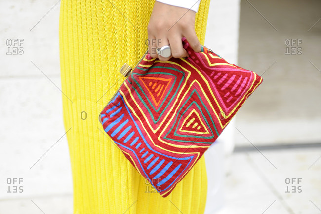 Woman in a yellow knit dress with a colorful geometric clutch purse