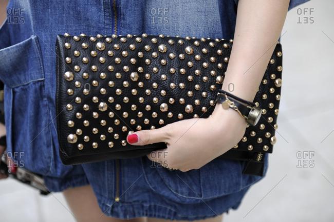 Woman in a denim jumper holding a black studded handbag