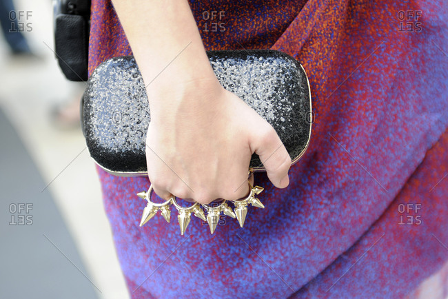Woman in a multi-colored dress with brass knuckles holding a black glitter clutch