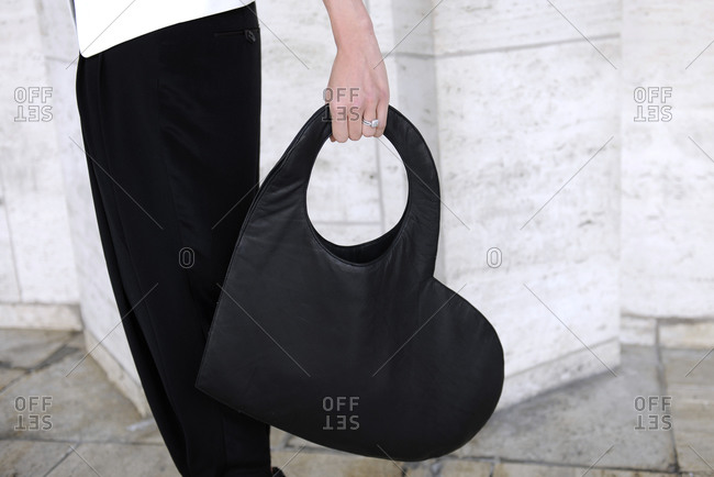 Woman standing on a sidewalk holding a black leather heart-shaped purse
