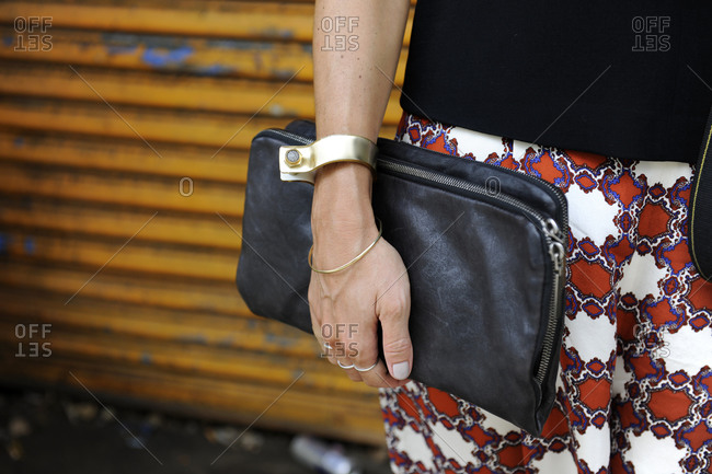 Woman in orange and blue patterned pants holding a black clutch purse