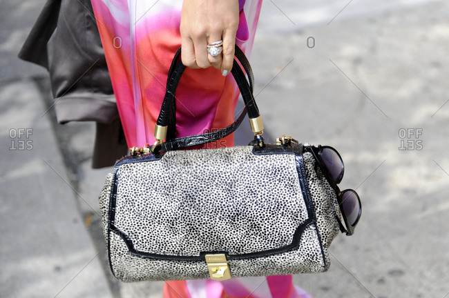 Woman in multi-colored pants holding a black dotted handbag