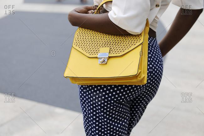 Woman in blue polka dot pants carrying a yellow handbag