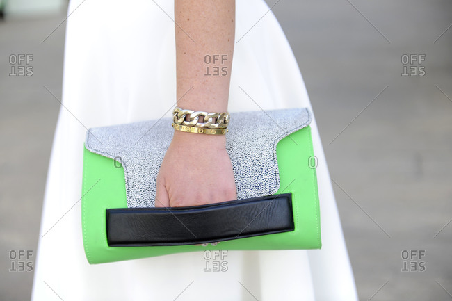 Woman in a white dress carrying a green and blue clutch purse