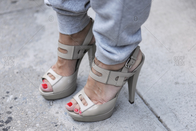 Woman in gray cuffed sweatpants and beige high heels