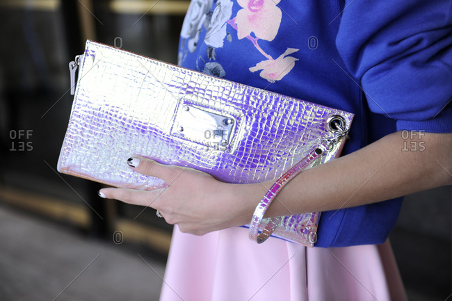 Woman in a blue shirt holding a silver iridescent clutch purse