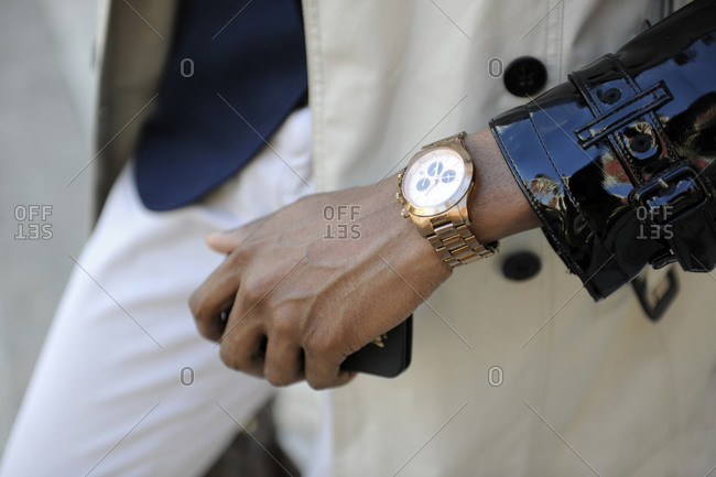 Person wearing a wrist watch and holding a mobile phone