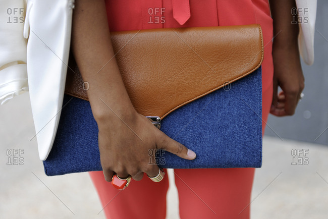 Woman in salmon colored pants holding a brown and blue clutch purse
