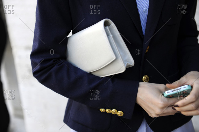 Woman carrying a handbag under her arm and holding a mobile phone