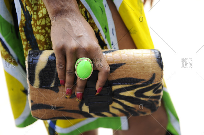 Woman with a chunky green ring holding a leopard print clutch purse