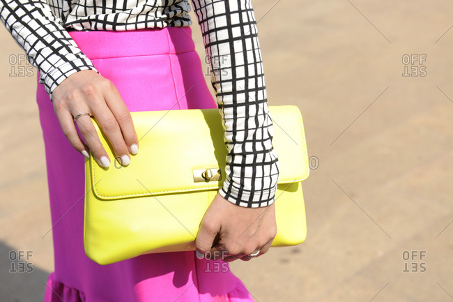 Woman in a bright pink skirt holding a yellow clutch purse
