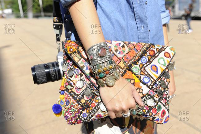 Woman in a denim shirt holding a bohemian patchwork clutch purse