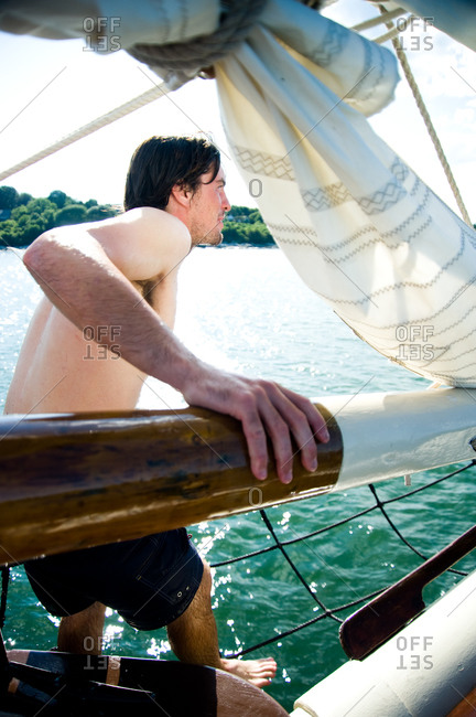 Mystic, CT, USA - July 26, 2010: Man readying himself to jump off the Mystic Whaler for a swim