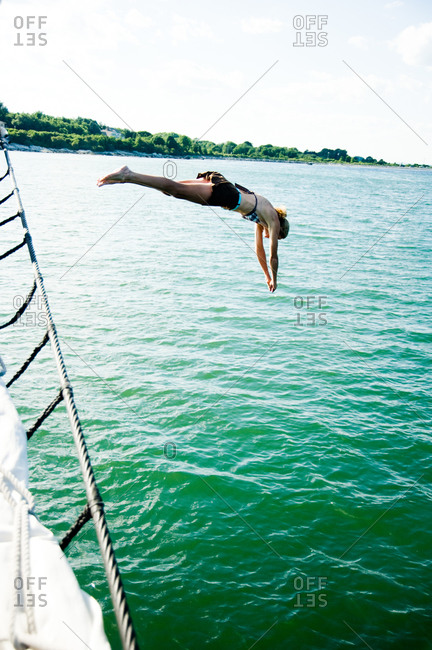 Woman diving off sailboat into the ocean
