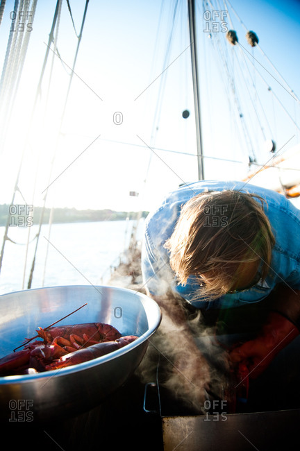 Person cooking lobster aboard a sailboat