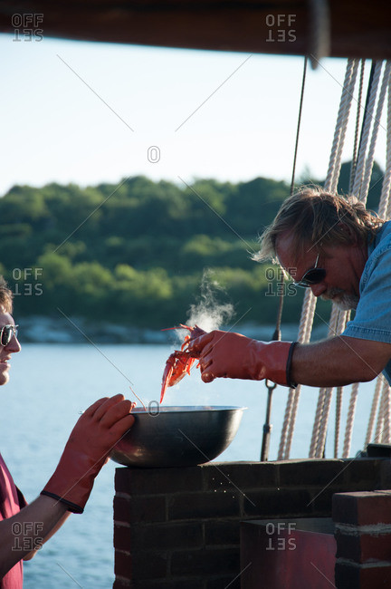 Mystic, CT, USA - July 26, 2010: Cook putting a steaming lobster in bowl for a dinner aboard the Mystic Whaler