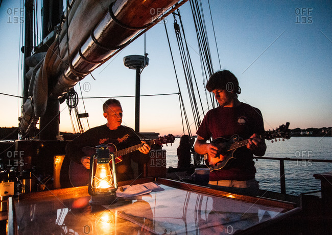 Mystic, CT, USA - July 26, 2010: Men playing music aboard the Mystic Whaler at dusk