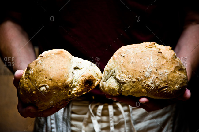Man holding two crusty loaves of bread