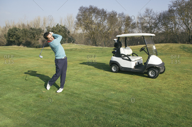Golfer on a golf course with a golf cart