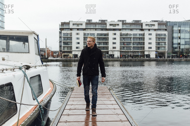 Smiling young man with a book walking on a jetty in winter