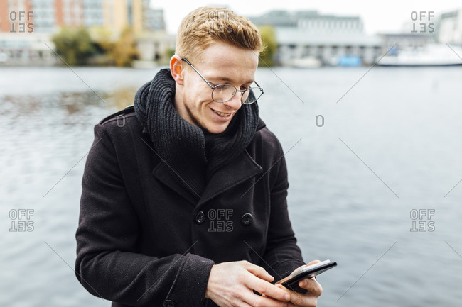 Smiling young man looking at his smartphone in front of the water