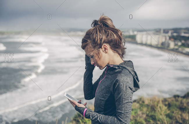 Portrait of mid adult sportive woman using smart phone