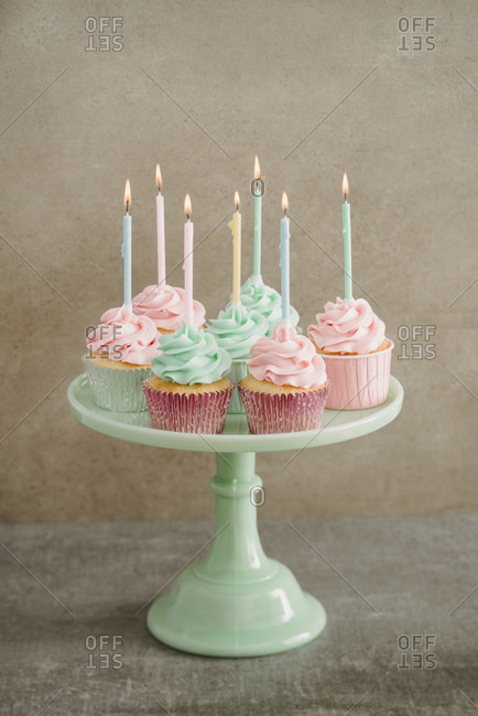 Cup cakes with lighted candles on a cake stand