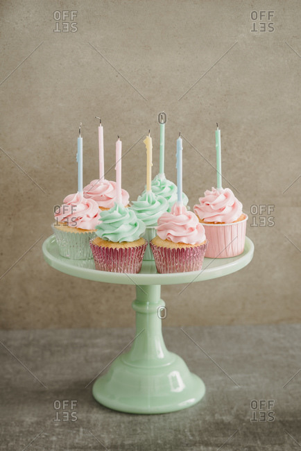 Cup cakes with candles on a cake stand