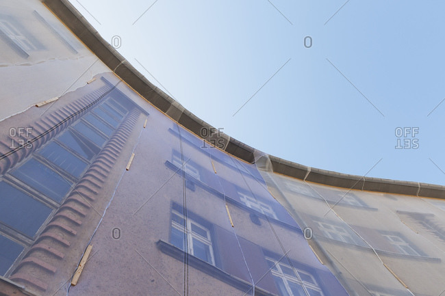 Facade of multi-family house under restoration covered with nets