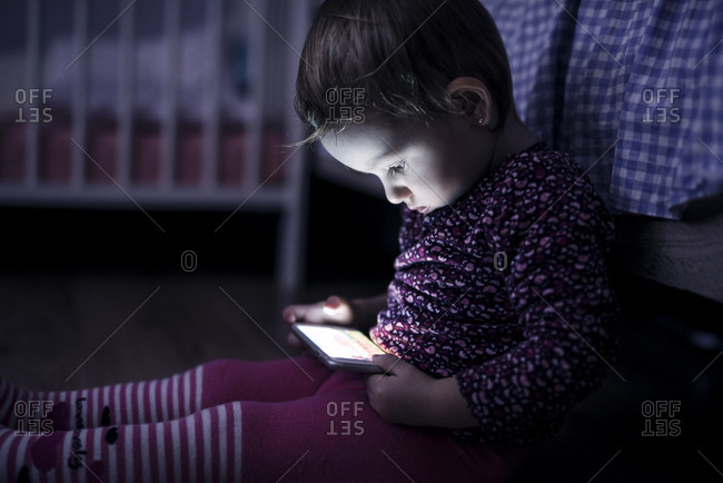 Toddler sitting on the floor playing with smartphone
