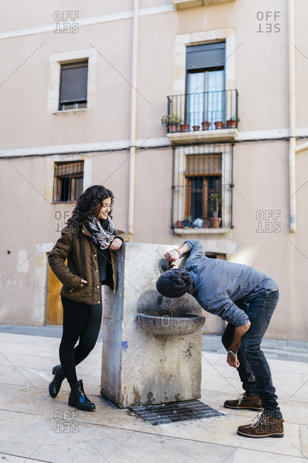 Spain, Tarragona, Young couple, man drinking from drinking fountain