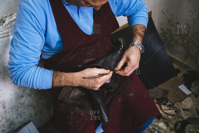 Shoemaker repairing a shoe in his  workshop